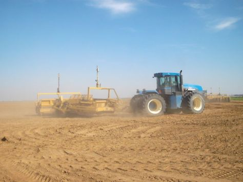 Large tractor land leveling a field